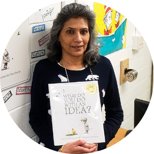 Mrs. Singhal holding a book